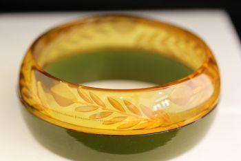 Art Deco Era Bakelite bangle, bracelet features a laminated section of reverse carved apple juice and avocado Bakelite.